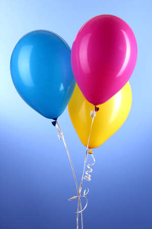 Three colorful balloons on blue background photo
