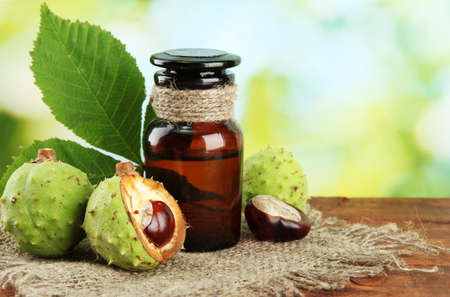 botanical medicine: medicine bottle with chestnuts and leaves, on green background