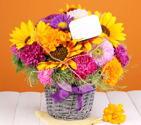 ronantic: Beautiful bouquet of bright flowers with paper note on wooden table on orange background