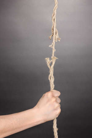 Breaking rope and hand on grey background photo