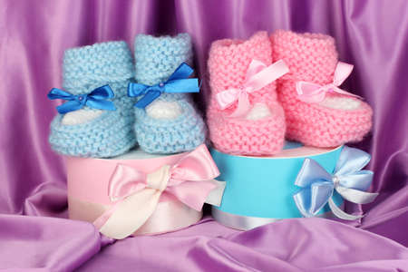 cuddly baby: pink and blue baby boots and gifts on silk background  Stock Photo