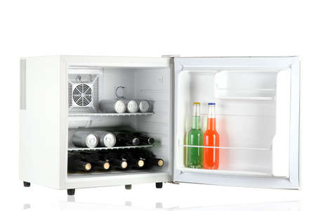 Mini fridge full of bottles of alcoholic beverages isolated on white photo