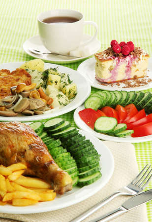 Roast chicken with french fries and  vegetables, cup of tea and dessert, on green table cloth photo