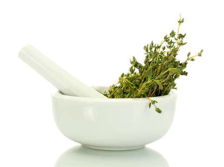 mortar with fresh green thyme isolated on white photo