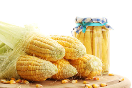 fresh corn and preserve corn on wooden cutting board, isolated on white photo