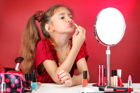 little girl in her mother's dress, is trying painting her lips Stock Photo - 15741295