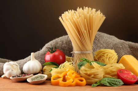 Pasta spaghetti, vegetables and spices, on wooden table, on brown background photo