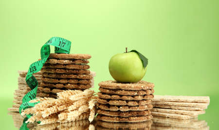 tasty crispbread, apple and measuring tape, on green background Stock Photo - 15414524