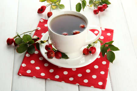 cup of tea with hip roses, on wooden table photo