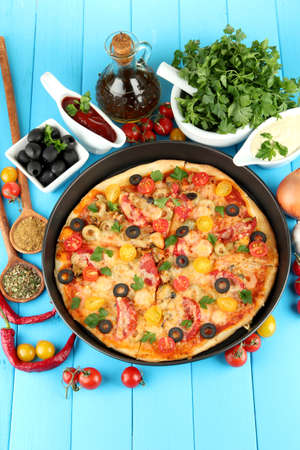 colorful composition of delicious pizza, vegetables and spices on blue wooden background close-up Stock Photo - 15414627