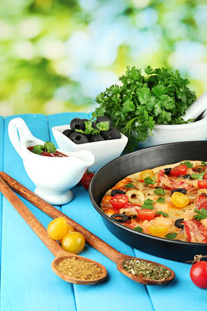 colorful composition of delicious pizza, vegetables and spices on blue wooden background close-up Stock Photo - 15414616