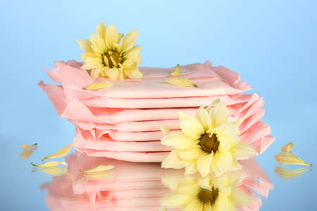 menses: Panty liners in individual packing and yellow flowers on blue background close-up