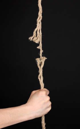 Breaking rope and hand isolated on black photo