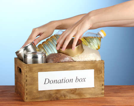 Donation box with food on blue background close-up photo
