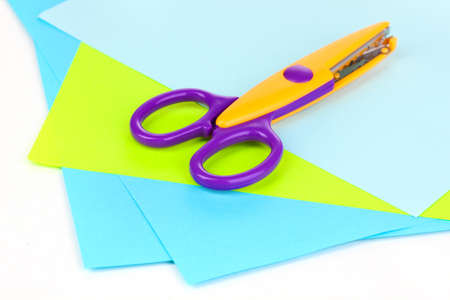prominence: Colorful zigzag scissors with color paper isolated on white Stock Photo