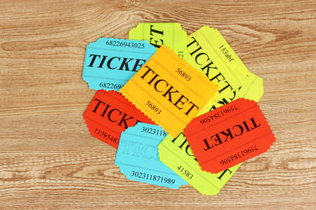 Colorful tickets on wooden background close-up photo