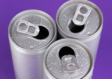 aluminum cans with water drops on purple background photo