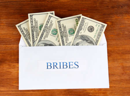 bribes: The envelope with the money bills on wooden background. Bribes. Stock Photo