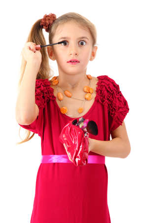 little girl in her mother's dress, is trying painting her eyelashes, isolated on white photo