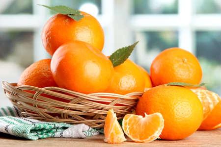 mandarijnen met bladeren in een mooie mand, op houten tafel op het venster achtergrond Stockfoto