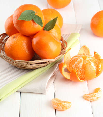tangerines with leaves in a beautiful basket, on white wooden table Stock Photo - 15443972