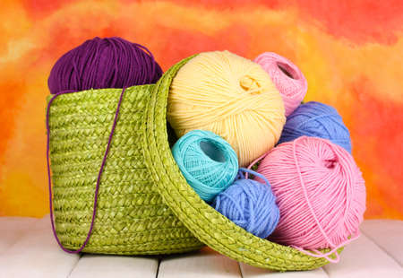 basket ball: Colorful yarn for knitting in green basket on white wooden table on colorful background