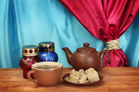 confect: Teapot with cup and saucer with  sweet halva on wooden table on a background of curtain close-up Stock Photo
