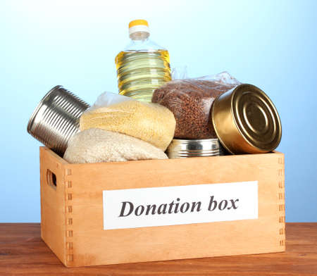 Donation box with food on blue background close-up Stock Photo - 15456174