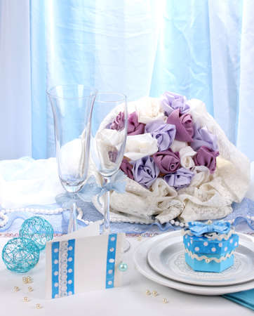 Serving fabulous wedding table in blue color on blue and white fabric background photo