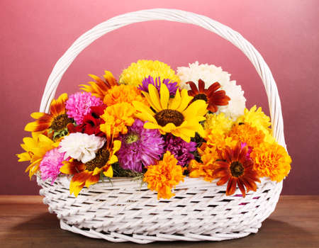 ronantic: Beautiful bouquet of bright flowers in white basket on wooden table on pink background