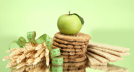 tasty crispbread, apple, measuring tape and ears, on green background Stock Photo - 15473810