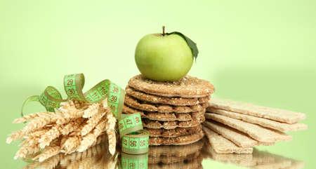 tasty crispbread, apple, measuring tape and ears, on green background Stock Photo - 15473810