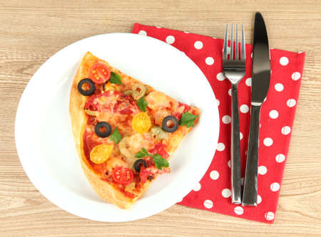 plate with a slice of delicious pizza on wooden background photo