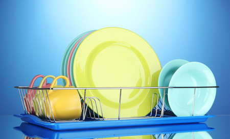 Color plates in rack on blue background photo