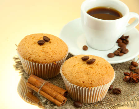 tasty muffin cakes with spices on burlap and cup of coffee, on beige background photo