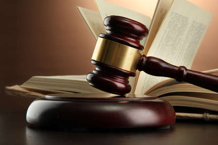 derecho penal: Mazo de madera y libro sobre la mesa de madera, sobre fondo marr�n