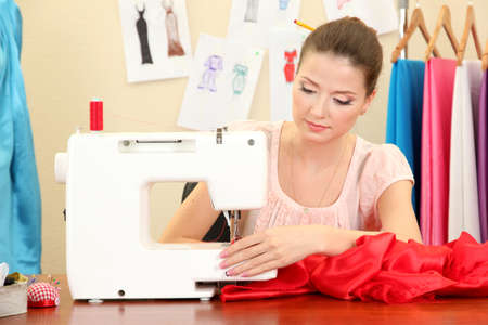 sew: beautiful young dressmaker in workroom Stock Photo