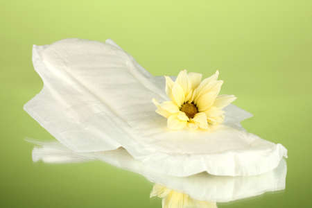 Panty liner and yellow flower on green background close-up Stock Photo - 15456260
