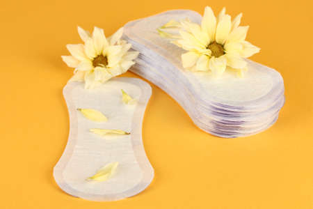 daily panty liners and yellow flowers on orange background close-up Stock Photo - 15456313