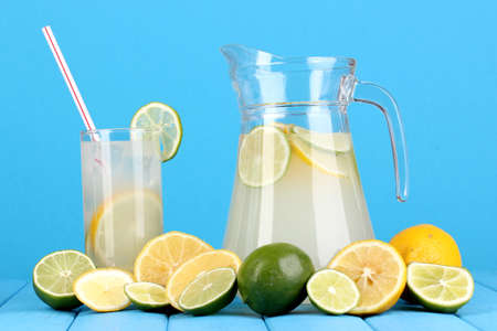 Citrus lemonade in pitcher and glass of citrus around on wooden table on blue background Stock Photo - 15456590
