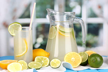 Citrus lemonade in pitcher and glass of citrus around on blue wooden table on window background Stock Photo - 15456618
