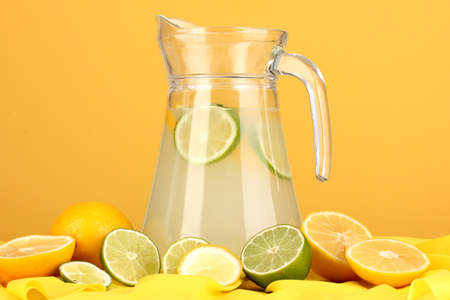Citrus lemonade in glass pitcher of citrus around on yellow fabric on orange background Stock Photo - 15456538