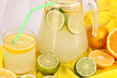 Citrus lemonade in glass and pitcher of citrus around on yellow fabric on white wooden table close-up Stock Photo - 15456634