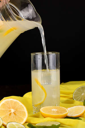 Citrus lemonade in glass and pitcher of citrus around on yellow fabric on wooden table close-up Stock Photo - 15456554