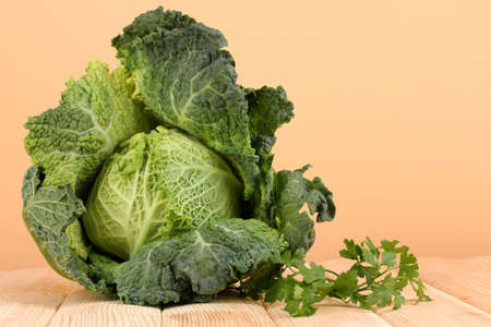 Fresh savoy cabbage on wooden table on beige background photo