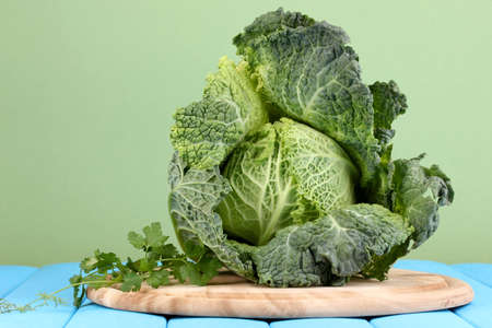 Fresh savoy cabbage on blue wooden table on yellow background photo