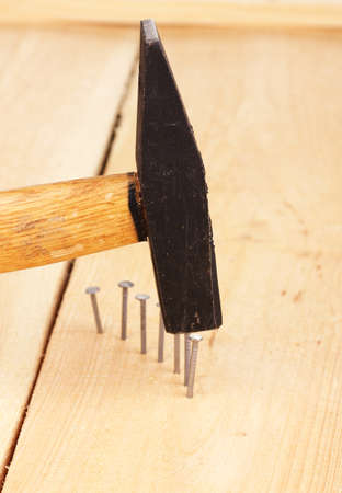 Metal nails in wooden plank and hammer photo