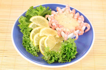 Delicious marinated shrimp with sauce served on plate on bamboo mat photo