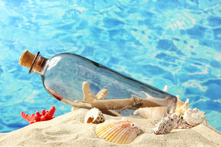 castaway: Glass bottle with note inside on sand, on blue sea background Stock Photo