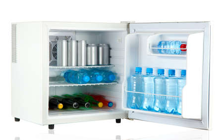 mini fridge full of bottles and jars with various drinks isolated on white photo